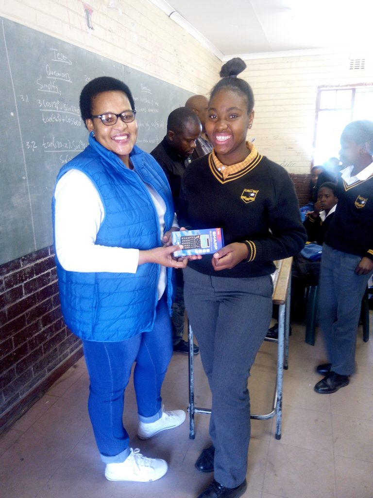 A student receiving her calculator from her teacher
